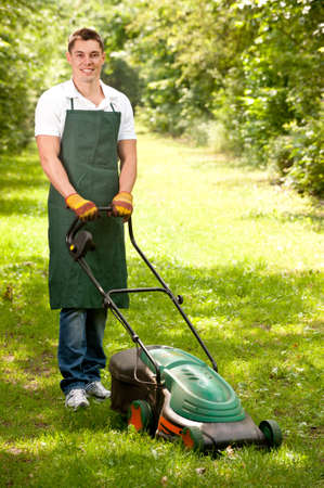 mowing grass: Young and smiling gardener with lawnmover Stock Photo