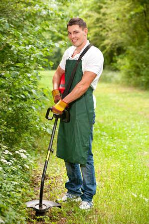 gras maaien: Jong en glimlachen tuinman met gazon trimmer