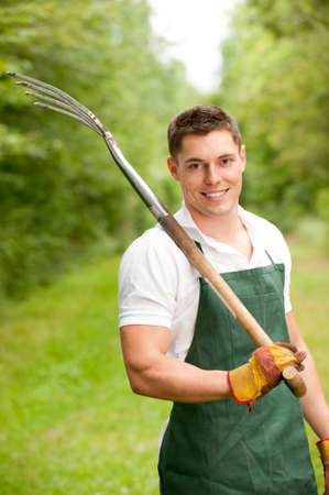gardening tool: Young and smiling gardener with pitchfork Stock Photo