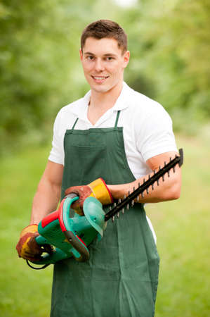 Young and smiling gardener with hedge cutter Reklamní fotografie