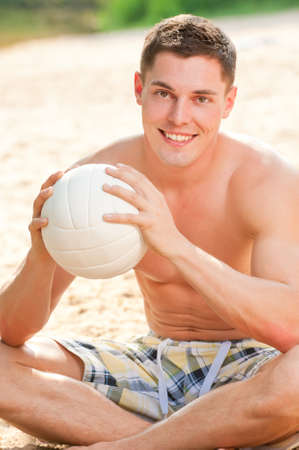 Young and smiling man with ball at the beach photo