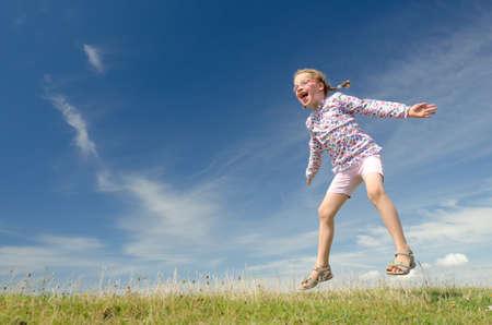 aire puro: Feliz niña saltando en frente de cielo azul