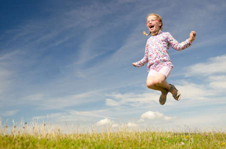 air jump: Happy little girl jumping in front of blue sky Stock Photo