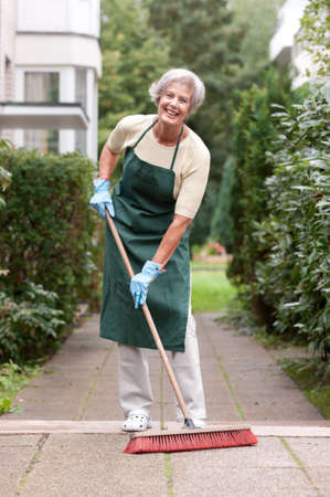 Active senior woman with broom Stock Photo - 10929242