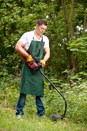 electric trimmer: Young and smiling gardener with lawn trimmer Stock Photo