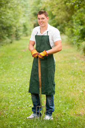 pitchfork: Young and smiling gardener with pitchfork Stock Photo