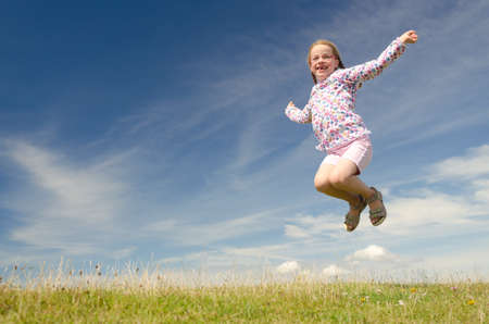 kids exercise: Happy little girl jumping in front of blue sky Stock Photo