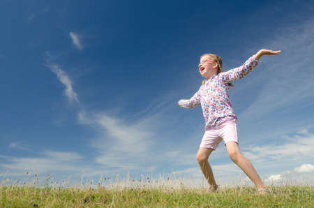 fresh air: Happy little girl jumping in front of blue sky Stock Photo