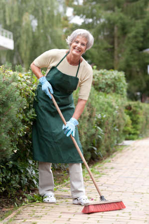 Active senior woman with broom