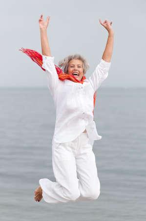 persona saltando: Mujer mayor activo y feliz