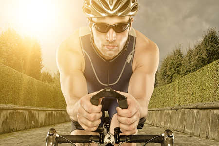 biker man: Young man with bike in sunset Stock Photo