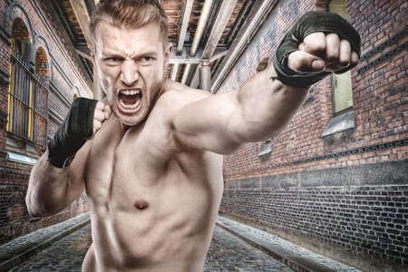 hombre fuerte: Joven boxeador en el frente de estilo urbano