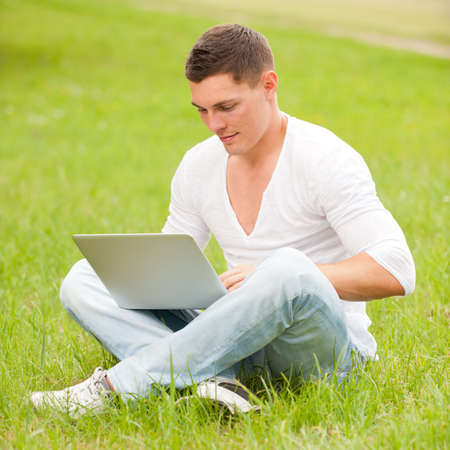 Young man with notebook in the park photo