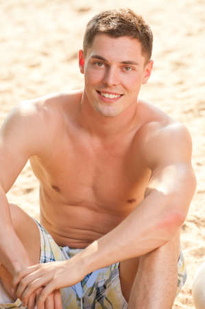 Young and smiling man at the beach photo
