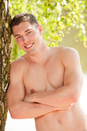shirtless male: Young and smiling man at the beach Stock Photo
