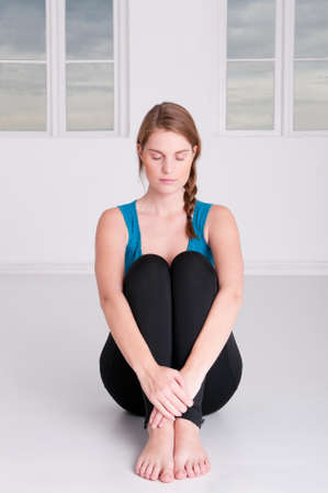 crossed legs: Young woman is doing some meditation in a white room Stock Photo