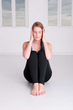 Young woman is doing some meditation in a white room photo