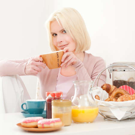 honey blonde: Young and beautiful woman having breakfast in the morning