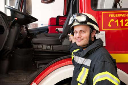 casco rojo: Foto de un bombero joven y exitoso en el trabajo