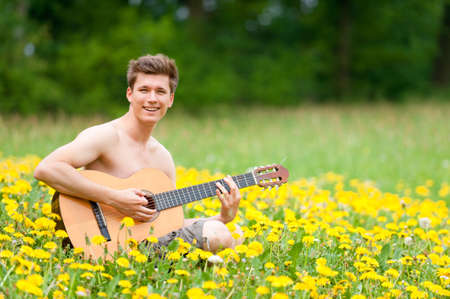 Smiling young man with guitar in the field photo