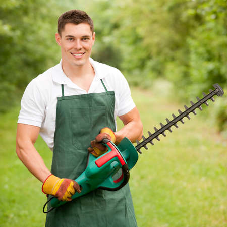 machine man: Young and smiling gardener with hedge cutter Stock Photo