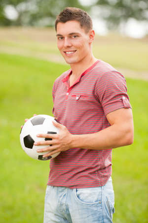 Young man with ball in the park photo