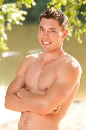 hombres sin camisa: Hombre joven y sonriente en la playa Foto de archivo