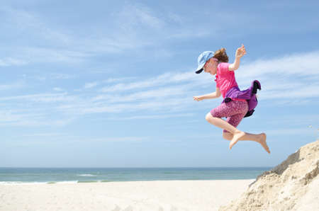 Little and happy girl jumping in front of blue sky