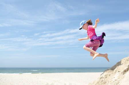 persona saltando: Ni�a feliz y saltando delante de cielo azul