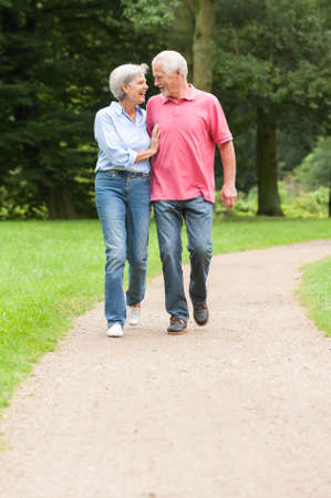 Active and happy senior couple walking in the park photo