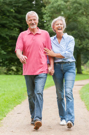 walking: Active and happy senior couple walking in the park