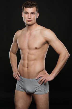 cuerpos desnudos: Hombre atractivo joven delante de fondo negro