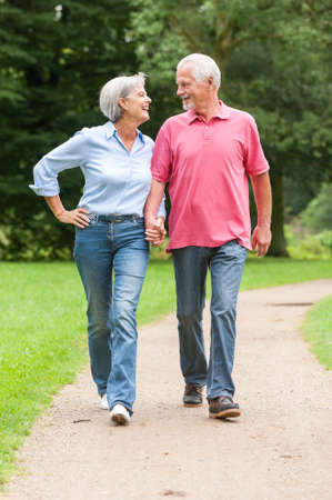 mature couple: Active and happy senior couple walking in the park