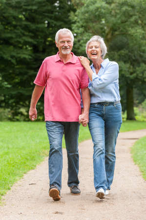 active couple: Active and happy senior couple walking in the park