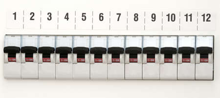 fuse box: Fuse block on a white wall with number 1 to 12