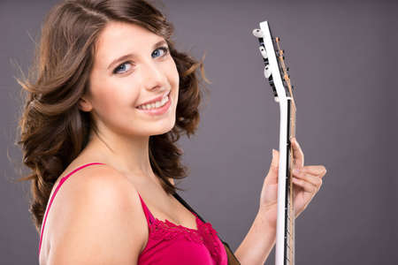 Young and smiling teenager with guitar in front of grey background photo