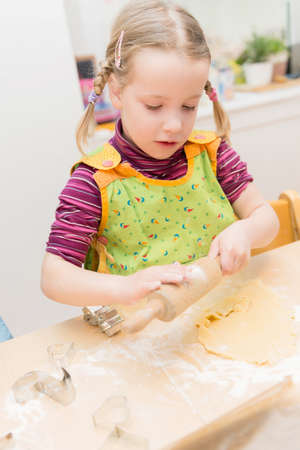 Little girl is baking some cookies in the kitchen photo