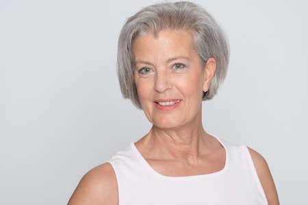 Ältere Frau in grauem Hintergrund