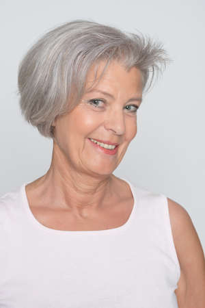 grey hair female: Senior woman in front of grey background