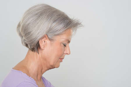 one eye closed: Senior woman in front of grey background