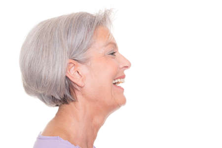 looking to the side: Smiling senior woman in front of white background