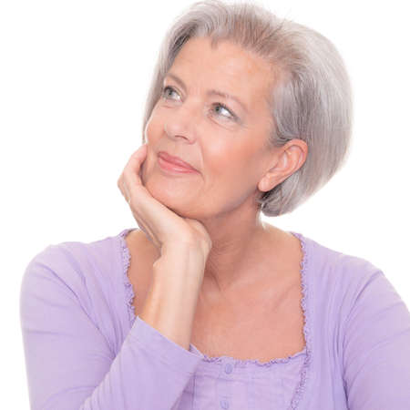Thinking senior woman in front of white background Stock Photo