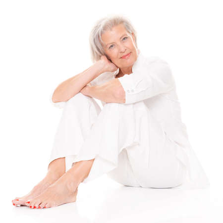 Sitting senior woman in front of white background Stock Photo