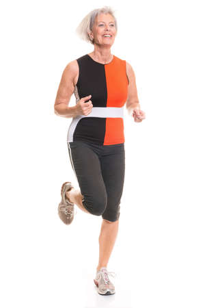 Running senior woman in front of white background Imagens