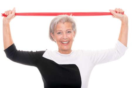 Mujer mayor con la banda de goma en frente de fondo blanco photo