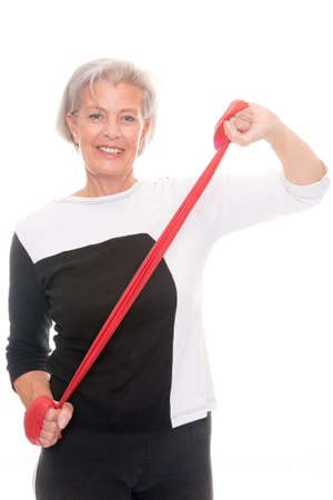 rubber band: Senior woman with rubber band in front of white background Stock Photo