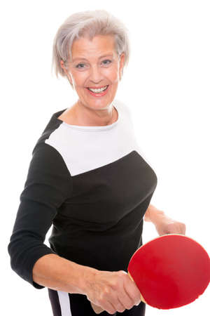 Active senior woman playing table tennis in front of white background photo
