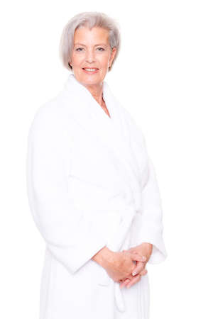 Senior woman with bathrobe in front of white background photo