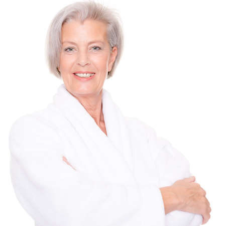 Senior woman with bathrobe in front of white background Imagens