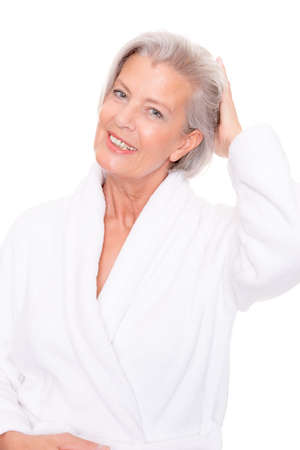 grey hair female: Senior woman with bathrobe in front of white background Stock Photo